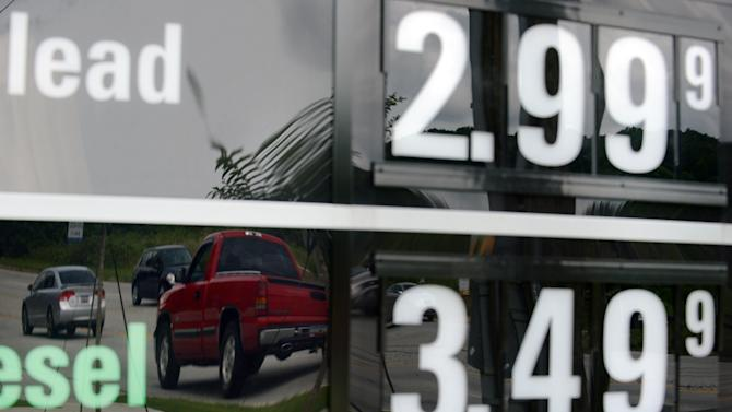 In this Monday, July 1, 2013 photo, vehicles are reflected in a sign advertising unleaded gas for $2.99 at a QuikTrip station in Greenville, S.C. Gasoline prices are on a summer slide, giving U.S. drivers a break as they set out for the beach and other vacation spots for the Fourth of July. (AP Photo/Rainier Ehrhardt)