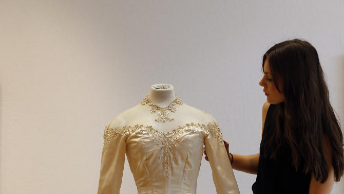 A Christie's employee adjusts Elizabeth Taylor's first wedding dress, designed by the legendary costume designer Helen Rose, at the auction house Christie's in London, Wednesday, June 19, 2013. The wedding dress is part of the auction 120 years of Pop Culture, which is showcasing important memorabilia dating from every decade of the past century of popular culture from the ubiquitous industries of film and music. The estimated price is 30,000 – 50,000 pound (46,000-78,000 dollars). (AP Photo/Frank Augstein)