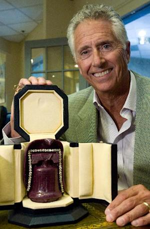 In this photo taken Thursday, Sept. 2, 2010, Jim Stein, owner of Stuart Kingston Jewelers, poses with a custom case holding the Liberty Ruby in Wilmington, Del. The U.S. Attorney's Office says four men have been arrested in connection with the theft of a $2 million ruby during a jewelry store heist in Wilmington, Del. Spokeswoman Kimberlynn Reeves said an indictment that had been returned in December against the suspects was unsealed Thursday, Feb. 20, 2014 after their arrest. The four are accused of robbing Stuart Kingston Jewelers in November 2011 and escaping with $4.4 million in jewelry, including the 5-inch, 4-pound Liberty Bell Ruby, made from the largest mined ruby in the world. The indictment says the armed, masked men restrained store employees with zip ties and duct tape and smashed glass display cases with hammers. Reeves said none of the jewelry has been recovered.(AP Photo/The Wilmington News-Journal, William Bretzger)