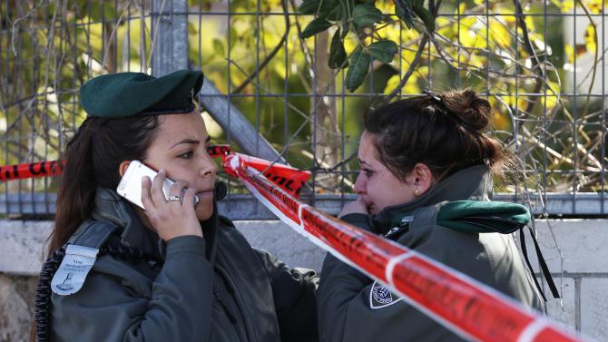 An Israeli border police woman is comforted by her colleague at the scene of an attack in Jerusalem