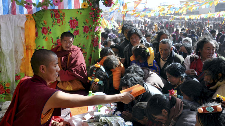 In this March, 2011 photo provided by Tibetan writer Tsering Woeser, Karma Tsewang, left, a highly regarded Tibetan monk, holds a Buddhist script as he offers Buddhist blessings to believers at a preaching center established by Japa Monastery in Nangqian county, Qinghai province, China. Tibetan writer Tsering Woeser said Friday, Dec. 27, 2013, Chinese authorities have detained the monk and 16 of his supporters, as Beijing tightens its grip over the region. The monk is known for his work on disaster relief, environmental protection and teaching youth the Tibetan language. The writer said Karma Tsewang was taken away by police Dec. 6 while traveling on business in the city of Chengdu. More than 100 laypeople and monks in Nangqian petitioned the government Dec. 18 to release Karma Tsewang, but 16 of them were detained in the following days, the writer said. (AP Photo/Tsering Woeser)