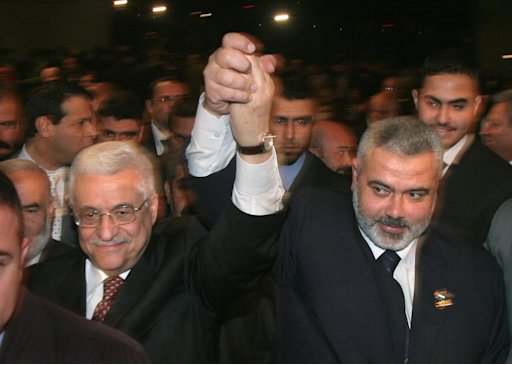 FILE - In this file photo taken on March 17, 2007, Palestinian Authority President Mahmoud Abbas, left, and  Prime Minister Ismail Haniyeh from Hamas, right, raise their linked arms as they move through the crowd at a special session of parliament in Gaza City. After four years of turbulent rule in the Gaza Strip, the Islamic militant group Hamas is weighing a new strategy of not directly participating in future governments even if it wins elections, an approach aimed at avoiding isolation by the world community and allowing for continued economic aid. (AP Photo/Hatem Moussa, File)