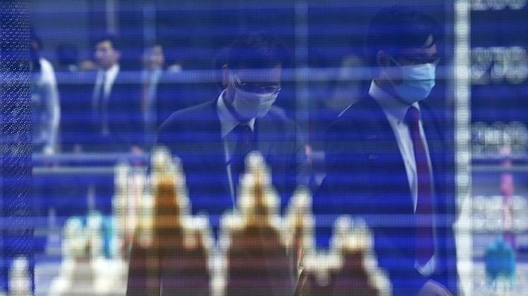 Men, wearing masks, are reflected on a screen displaying a graph showing movements of Shanghai B shares outside a brokerage in Tokyo