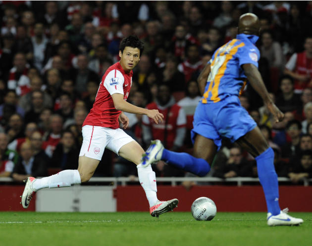 Arsenal's Ryo Miyaichi, left, runs with the ball during their English League Cup soccer match against Shrewsbury Town at the Emirates stadium, London, Tuesday, Sept. 20, 2011. (AP Photo/Tom Hevezi)