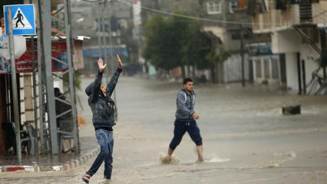 A Palestinian boy gestures as he stands at a flooded road following heavy rain in Gaza City