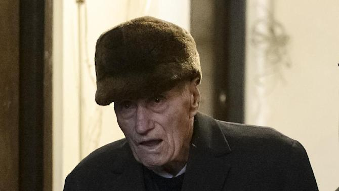 Former communist prison commander Alexandru Visinescu leaves his home scorted by a police officer, in Bucharest, Romania, Wednesday, Feb. 10, 2016. A Romanian appeals court has upheld a 20-year prison sentence for Visinescu, a 90-year-old communist-era prison guard convicted of crimes against humanity, the most high-profile case since dictator Nicolae Ceausescu was tried and executed in 1989. (AP Photo/Andreea Alexandru) ROMANIA OUT