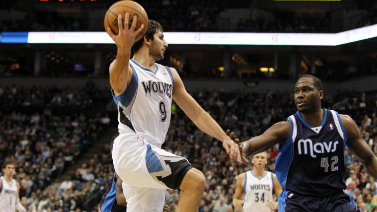 Minnesota Timberwolves point guard Ricky Rubio (9), of Spain, passes the ball around Dallas Mavericks power forward Elton Brand (42) during the first half on an NBA basketball game on Saturday, Dec. 15, 2012, in Minneapolis. Rubio was making his season debut after recovering from surgery on his left knee. (AP Photo/Genevieve Ross)