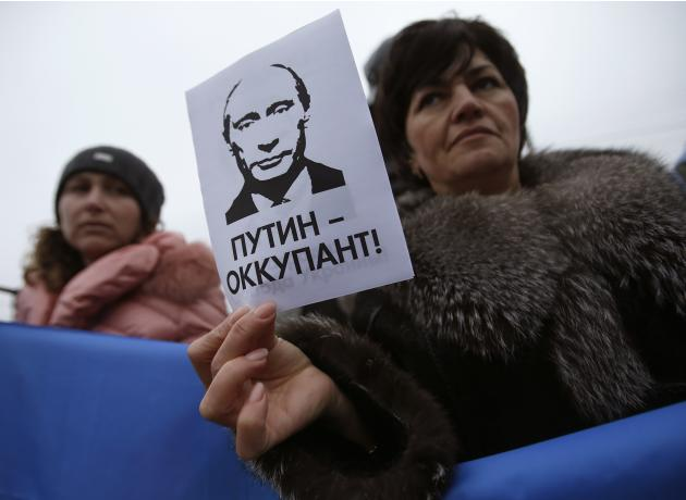 "A woman holds a sign with a portrait of Russian President Putin and the words ""Putin - Occupant"" during a pro-Ukrainian rally in Simferopo"