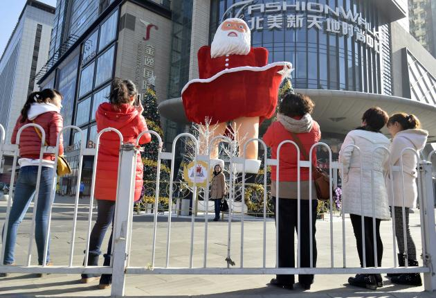 Women take pictures in front of a Santa Claus figure in Taiyuan