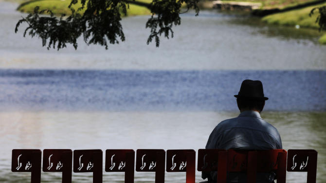 A man sits on a bench in the shade on a riverside path Wednesday, June 27, 2012, in Omaha, Neb. The National Weather Service issued heat warnings and advisories for southeast Nebraska and much of Iowa Wednesday as temperatures neared 100. (AP Photo/Kiichiro Sato)
