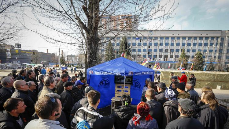 Pro-Russian supporters watch a broadcast of a Russian television in their camp near the seized office of the SBU state security service in Luhansk, eastern Ukraine