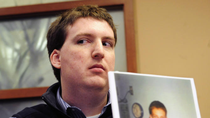 FILE - In this Dec. 8, 2011 file photo, Zach Tomaselli, 23, holds a photo of himself and his brother taken at about the time he claims he was was sexually abused in 2002 by former Syracuse basketball coach Bernie Fine, at a news conference in Pittsburgh. Federal authorities have dropped their investigation into sexual abuse claims that cost Fine his job, threw a top-ranked team into turmoil and threatened the career of Hall of Fame coach Jim Boeheim. After a probe spanning nearly a year, U.S. Attorney Richard Hartunian said Friday, Nov. 9, 2012 there was no evidence to support claims that Fine had molested a boy in 2002 in a Pittsburgh hotel room. The investigation erupted in the glare of a spotlight on child abuse shone by the Penn State University scandal that broke shortly beforehand, when Davis and Lang accused the longtime assistant of fondling them when they were teens.  (AP Photo/John Heller, File)