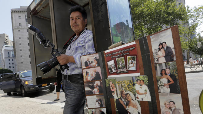 Wedding photographer Braulio Cuenca stands by a display of his wedding photography outside New York's Office of the City Clerk, as he waits for prospective clients, Wednesday, Aug. 7, 2013. (AP Photo/Richard Drew)