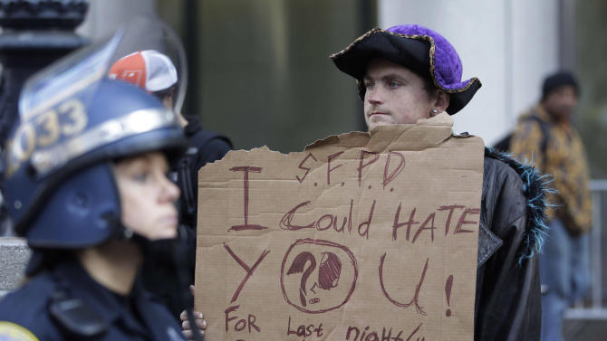 Occupy Wall Street demonstrator Brandon Brown holds a sign in front of police during a rally in San Francisco, Wednesday, Dec. 7, 2011, outside the encampment that was closed by authorities earlier in the day. Brown said he was arrested during the early-morning raid. (AP Photo/Paul Sakuma)