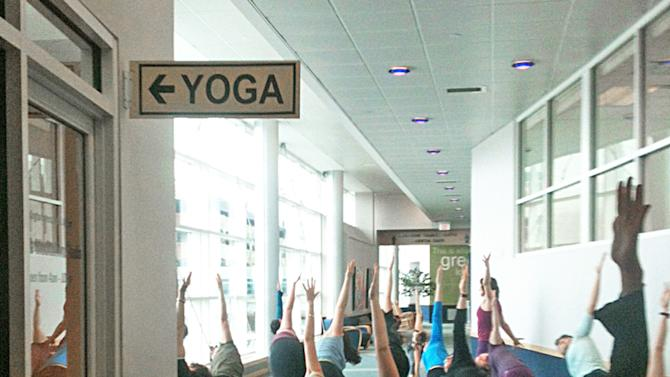This Jan. 12, 2013 photo shows a local class does yoga at the Burlington International Airport in Burlington, Vt., to celebrate the grand opening of a yoga space for travelers.  The airport is one of at least three airports offering a space for travelers to practice yoga while waiting for flights to make their trip more relaxing..(AP Photo/Lisa Rathke)