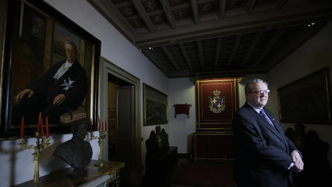 In this Tuesday, Jan. 29, 2013 photo, Grand Master Matthew Festing poses for a picture at the end of an interview with The Associated Press at the Magistral Palace of the Order of Malta in Rome's Via Condotti. It's an ancient Roman Catholic religious order that boasts diplomatic relations with 100-plus countries, an aid group that runs hospitals, ambulance services and old folks' homes on six continents, and a nominally sovereign entity that issues its own stamps, coins, license plates and passports, yet has no state to call home.  The Sovereign Military Order of Malta is all those things, and this week marks its 900th anniversary as a Vatican-recognized religious order dedicated to caring for the poor, sick and destitute around the globe. (AP Photo/Gregorio Borgia)