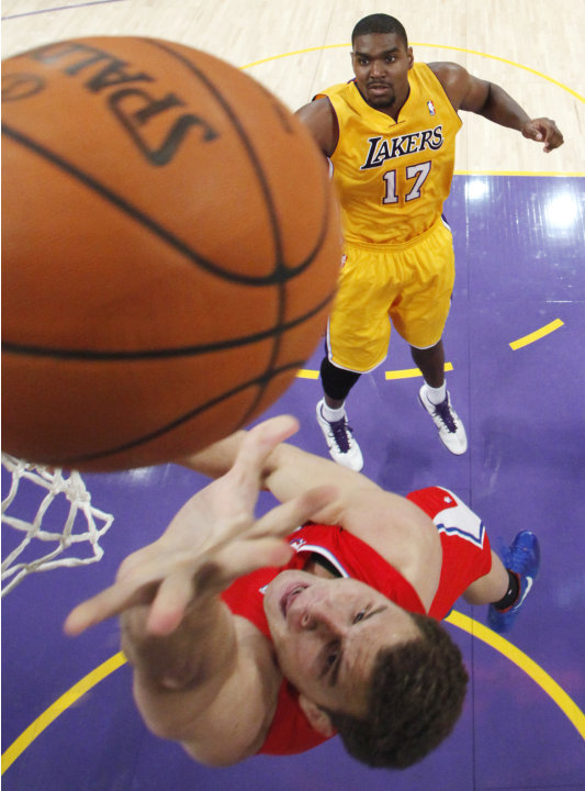 Los Angeles Clippers' Blake Griffin shoots the ball as Los Angeles Lakers' Andrew Bynum looks on during the first half of an NBA preseason basketball game in Los Angeles on Monday, Dec. 19, 2010. (AP