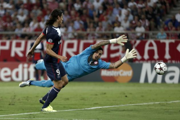 Paris St Germain's Cavani scores a goal against Olympiakos' goalkeeper Roberto during their Champions League soccer match at Karaiskaki stadium in Piraeus