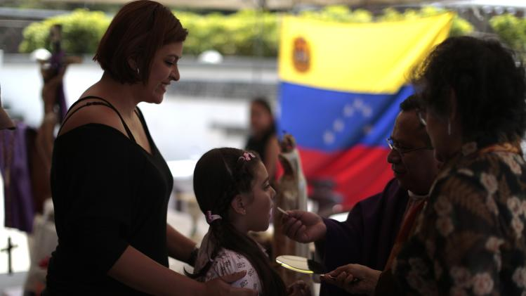 A child who is a member of the Venezuelan community in Guatemala take communion in a mass for peace in Venezuela, in Guatemala City