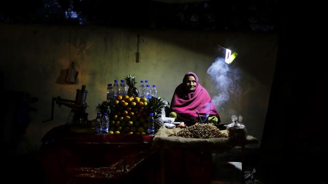 An elderly Indian roadside vendor, draped in a shawl, waits for customers in New Delhi, India, Thursday, Dec. 18, 2014. Chilly conditions persists in most parts of north India. (AP Photo/Altaf Qadri)