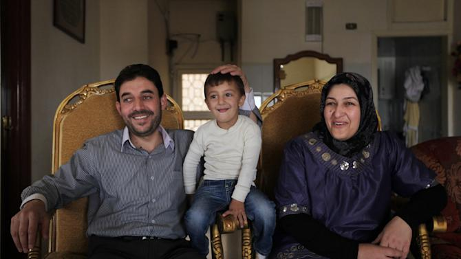 In this Tuesday, Oct. 2, 2012 photo, Bassel Hojeiri, 37, principal of the local middle school, with his wife, Hanan, and their son Muhammed, speak at his house during an interview with The Associated Press, in Arsal, a Sunni Muslim town eastern Lebanon near the Syrian border. This Lebanese border town has become a safe haven for war-weary Syrian rebels, a way station for wounded fighters and home to hundreds of frightened Syrian refugee families. Residents of Arsal, a Sunni Muslim town of 40,000, have strong motives to help those trying to topple Syria's brutal regime: they themselves were harassed and abused by it during three decades of de facto Syrian control of Lebanon. (AP Photo/Bilal Hussein)
