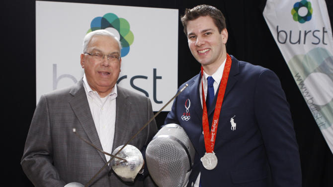 """COMMERCIAL IMAGE -  In this photograph taken by AP Images for Burst, U.S. Olympic fencer Tim Morehouse, right, who will use mobile video solution Burst during this summer's Olympic Games, stands with Boston Mayor Thomas M. Menino during the unveiling of the """"Burst from Behind the Scenes in London"""" program, hosted by Boston start-up Burst and Boston Properties, at the Shops at the Prudential Center, Thursday, July 5, 2012, in Boston.  (Bizuayehu Tesfaye/AP Images for Burst)"""