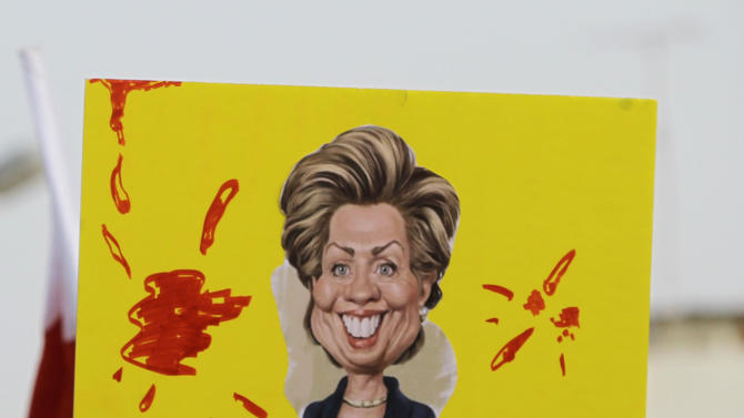 """In this photo taken May 17, 2012, Bahraini anti-government protesters carry a sign with a caricature of U.S. Secretary of State Hillary Clinton during a march in the northern village of Diraz, Bahrain. The sign reads: """"The American administration supports dictatorship in Bahrain."""" During one of the nightly clashes with Bahrain's security forces, a new chant broke out among opposition protesters: """"The U.S. is the big devil."""" A few days later, pro-government marchers also waved their fists against Washington. Both sides in the Bahrain meltdown are finding a shared target in the United States. (AP Photo/Hasan Jamali)"""