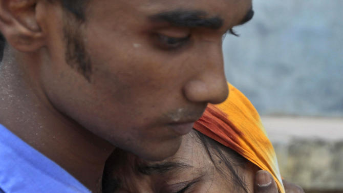 Relatives mourn a victim at the site where an eight-story building housing several garment factories collapsed in Savar, near Dhaka, Bangladesh, Wednesday, April 24, 2013. Dozens were killed and many more are feared trapped in the rubble. (AP Photo/ A.M. Ahad)
