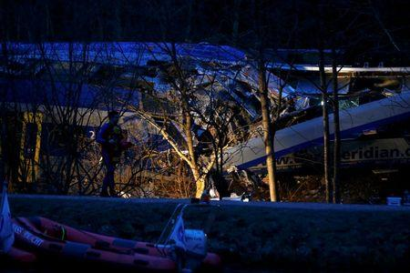 A member of emergency services walks at the site of two crashed trains near Bad Aibling in southwestern Germany