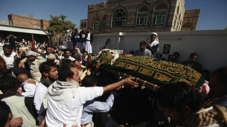 People carry bodies of Abdul Jalil Mohammed Noman Noman and wife Asma Ali Mohamed Noman, victims of a bombing of the Ministry of Defence compound during a funeral in Sanaa