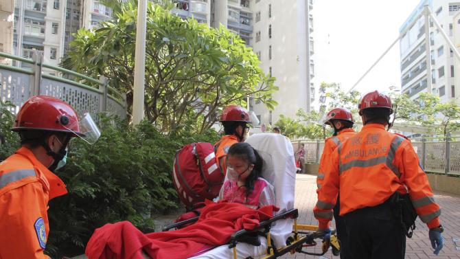An injured person is wheeled by rescue workers after a gas explosion at a public housing unit in Hong Kong