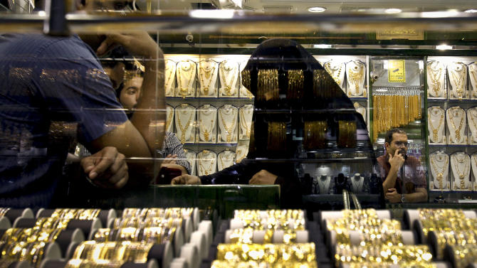 In this Thursday Oct. 11, 2012 photo, an Emirati woman discusses her purchases with a salesman at a jewelry shop in gold suq in Dubai, United Arab Emirates. With low customs on gold imports, low labor charges, cheap prices and high quality, Dubai has become one of the world's best retail gold jewelry markets. (AP Photo/Kamran Jebreili)