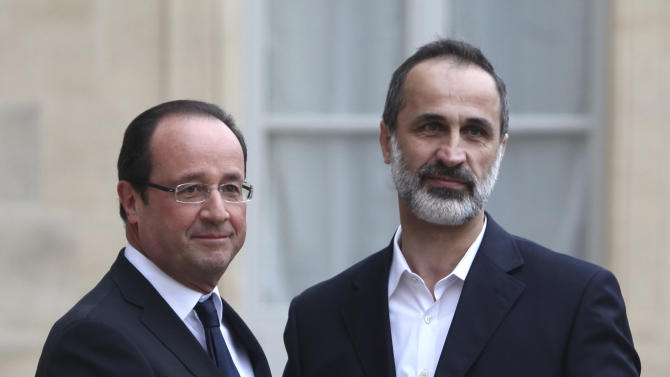 French President Francois Hollande, left, and head of the new Syrian National Coalition for Opposition and Revolutionary Forces Mouaz al-Khatib, right, pose for photos prior to a meeting, at the Elysee Palace, in Paris, Saturday, Nov. 17, 2012. France has taken a leading role among Western countries in supporting Syria's rebels. On Tuesday, it became the first Western nation to formally recognize Syria's newly formed opposition coalition as the sole legitimate representative of the Syrian people. (AP Photo/Thibault Camus)