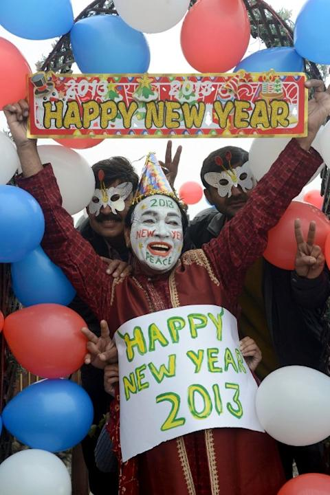 Indian revellers hold placards in Amritsar on December 31, 2012. Sydney will kick off a wave of dazzling firework displays welcoming in 2013, from Dubai to Moscow and London, with long-isolated Yangon