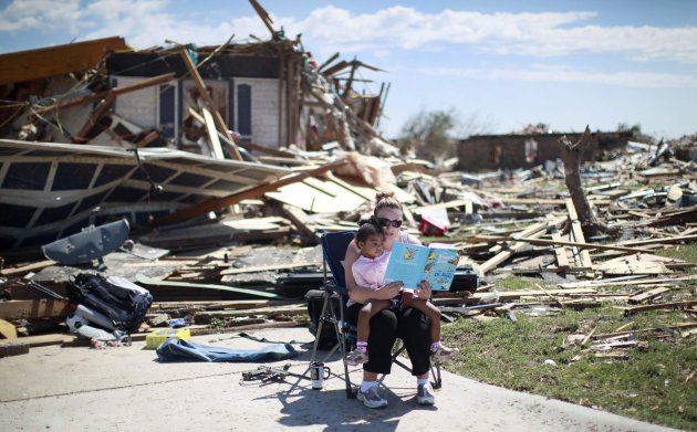 Sarah Dick reads a Doctor Seuss book to her three-year-old daughter Jadyn at the driveway of her tornado-destroyed house in Oklahoma City