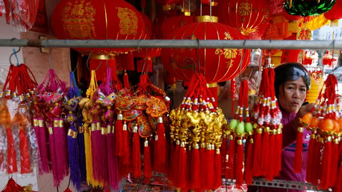 A woman looks at decorations at a market ahead of the Chinese Lunar New Year in central Phnom Penh