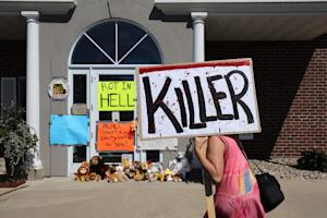 Protesters stand in the parking lot of Dr. Walter Palmer's …