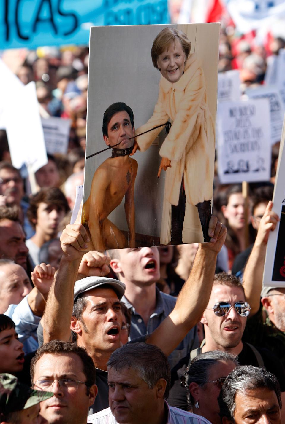 A protestor holds a collage showing German Chancellor Angela Merkel and Portuguese Prime Minister Pedro Passos Coelho during a workers unions' demonstration at Lisbon's Comercio Square, Saturday, Sept. 29 2012. Thousands of Portuguese enduring deep economic pain from austerity cuts took to the streets Saturday in protest. (AP Photo/Joao Henriques)