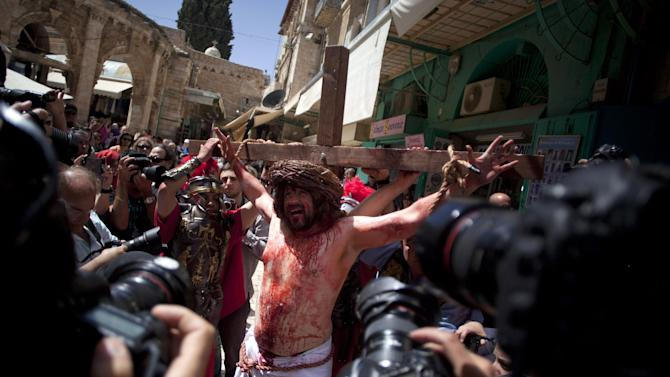 A Christian pilgrim dressed as Jesus Christ is attached to a cross during a reenactment of the crucifixion during a Good Friday procession in Jerusalem's Old City, Friday, March 29, 2013.  Less than 2 percent of the population of Israel and the Palestinian territories is Christian, mostly split between Catholicism and Orthodox streams of Christianity. Christians in the West Bank wanting to attend services in Jerusalem must obtain permission from Israeli authorities. Israel's Tourism Ministry said it expects some 150,000 visitors in Israel during Easter week and the Jewish festival of Passover, which coincide this year. (AP Photo/Sebastian Scheiner)