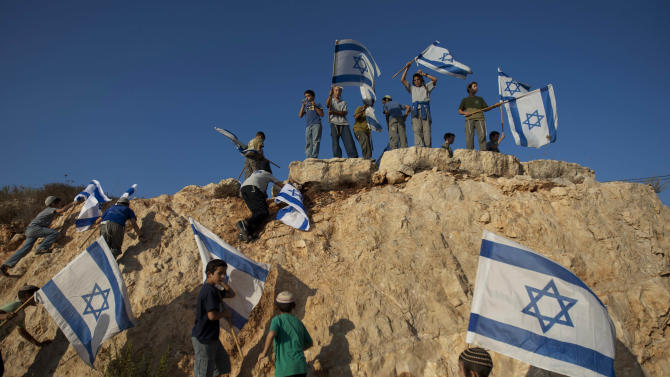 File - In this Sept. 20, 2011file photo, Israeli settler youths wave Israeli flags at the start of a protest march against Palestinian statehood, from the West Bank Jewish settlement of Itamar near the Palestinians town of Nablus. Palestinian Israel is going ahead with plans to build more than 1,000 settler homes in the West Bank, a spokesman said Thursday, a step that drew criticism from the Palestinians and may pose a challenge to peace efforts by Secretary of State John Kerry. (AP Photo/Ariel Schalit, File)