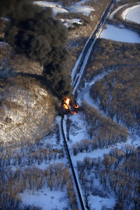 Smoke and flames erupt from the scene of a train derailment Thursday, March 5, 2015, near Galena, Ill. A BNSF Railway freight train loaded with crude oil derailed around 1:20 p.m. in a rural area where the Galena River meets the Mississippi, said Jo Daviess County Sheriff's Sgt. Mike Moser. (AP Photo/Telegraph Herald, Mike Burley)
