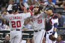 Washington Nationals Ian Desmond (20) is greeted at home plate by teammate Jayson Werth (28) as Atlanta Braves catcher Christian Bethancourt, right, looks on after Desmond's two-run homer during the sixth inning of a baseball game Tuesday, Sept. 16, 2014, in Atlanta. (AP Photo/David Tulis)