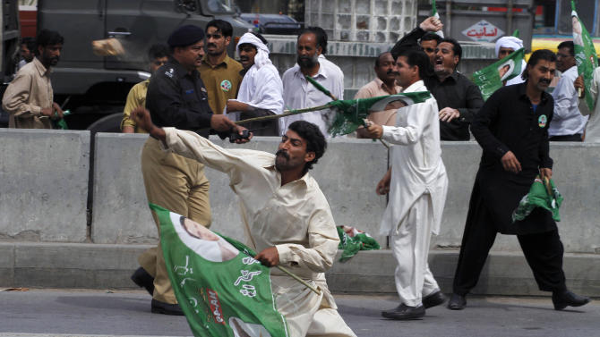 A supporter of Pakistan's former President and military ruler Pervez Musharraf hurls a stone towards the lawyers outside an anti-terrorism court, where Musharraf appeared in Rawalpindi, Pakistan, Tuesday, April 23, 2013. Musharraf appeared before anti-terrorism court over the assassination of former prime minister Benazir Bhutto's case, official said.  (AP Photo/Anjum Naveed)