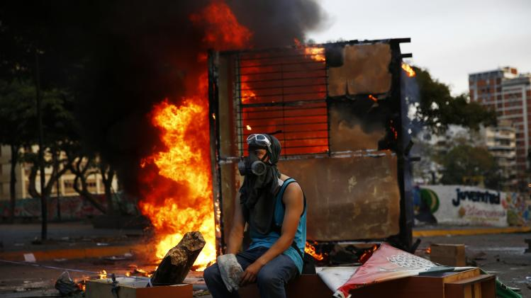 An anti-government protester sits next to a burning kiosk during a protest at Altamira square in Caracas