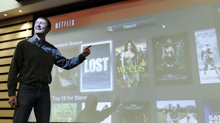 In this March 20, 2012, photo, Netflix Chief Product Officer Neil Hunt points out popular movies on Netflix at a theater inside Netflix headquarters in Los Gatos, Calif. A big part of Netflix's future rides on how much their engineers can improve the software that draws up lists of TV shows and movies that might appeal to each of the video-subscription service's 26 million customers. Netflix has spent 13 years learning viewers' disparate tastes so it can point out movies they might enjoy. (AP Photo/Paul Sakuma)