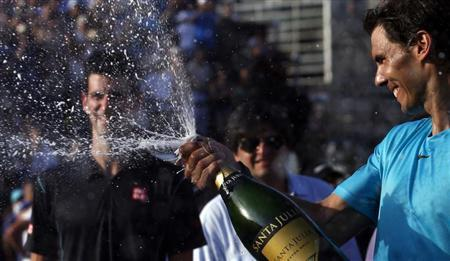 Rafael Nadal of Spain sprays champagne after defeating Novak Djokovic of Serbia in their exhibition tennis match in Buenos Aires