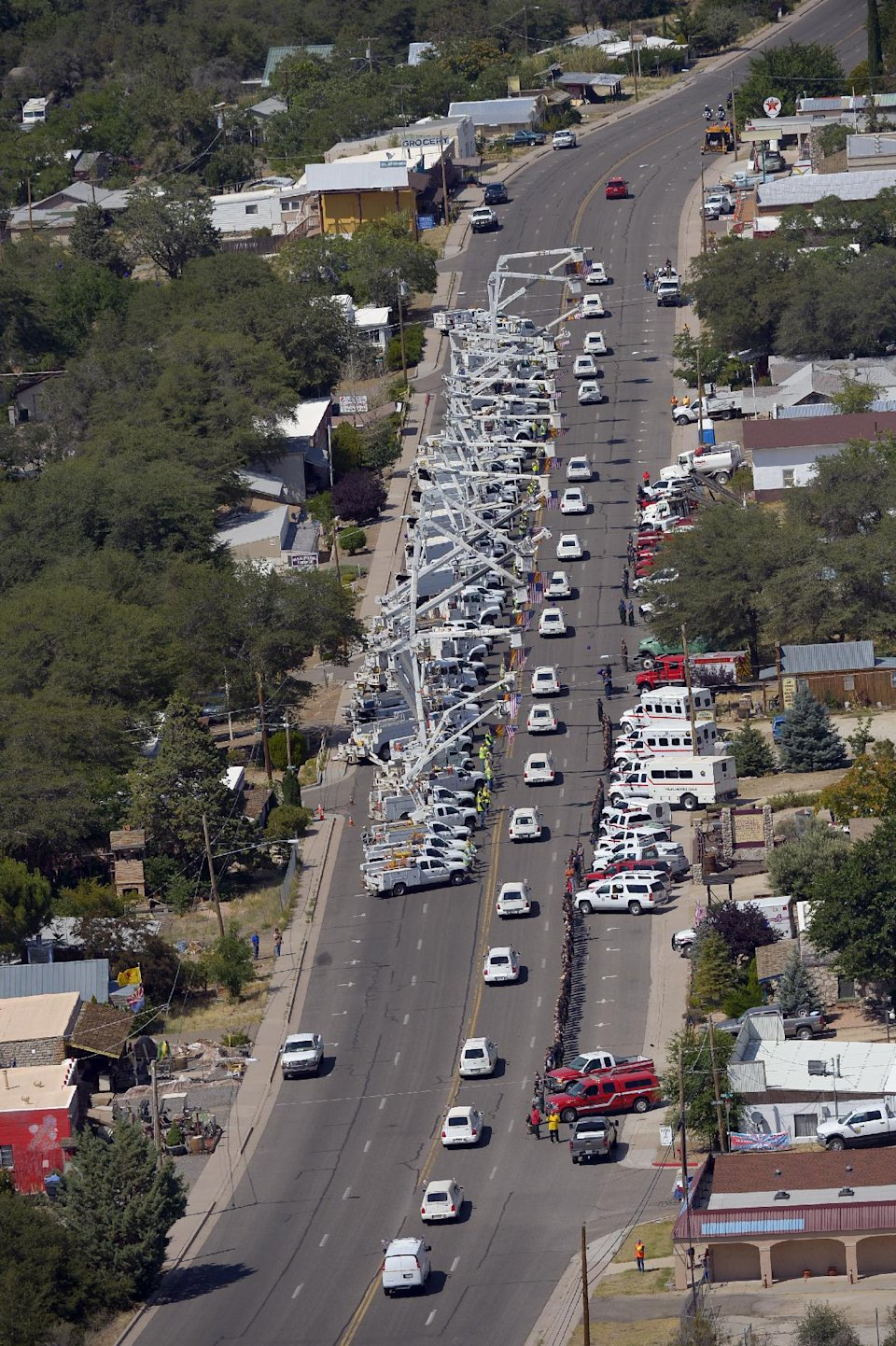 A procession of 19 hearses drives by, Sunday, July 7, 2013, in Yarnell, Ariz, The elite crew of firefighters were overtaken by the out-of-control blaze as they tried to protect themselves from the flames under fire-resistant shields last Sunday. (AP Photo/Mark J. Terrill)