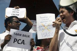 Members of SUARAM hold up placards during a protest against the new amendments in the PCA outside the parliament house in Kuala Lumpur