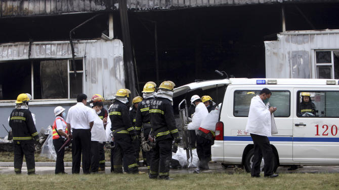 Firefighters and medical staff prepare to remove body bags that appears to contain the bodies of those killed by a fire at a poultry processing plant in northeast China's Jilin province's Mishazi township on Monday, June 3, 2013. The massive fire broke out at the poultry plant early Monday, trapping workers inside a cluttered slaughterhouse and killing over a hundred people, reports and officials said. (AP Photo) CHINA OUT