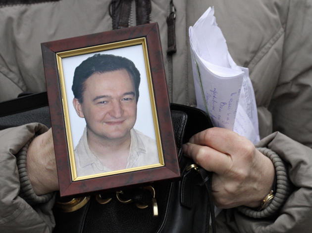 In this Monday, Nov. 30, 2009 file photo a portrait of lawyer Sergei Magnitsky who died in jail, is held  by his mother Nataliya Magnitskaya, as she speaks during an  interview with the AP in Moscow.